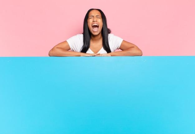 若い女性は積極的に叫び、非常に怒っている、イライラしている、憤慨している、またはイライラしているように見えます。