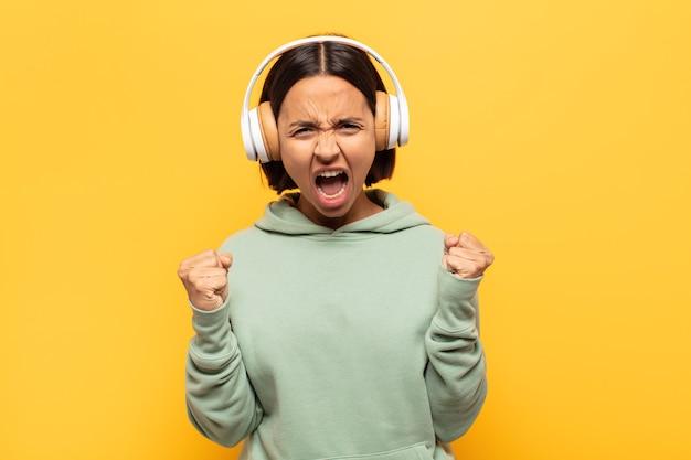 Молодая женщина агрессивно кричит с гневным выражением лица или со сжатыми кулаками празднует успех