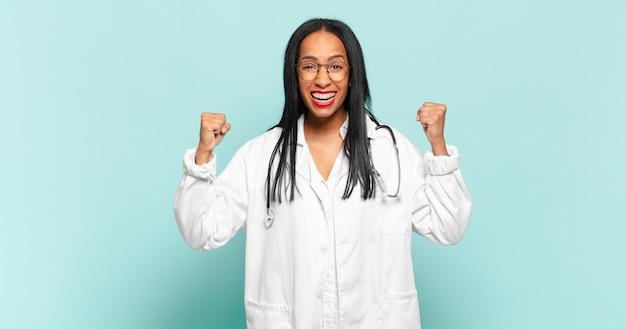 화난 표정으로 또는 주먹으로 공격적으로 외치는 젊은 여성이 성공을 축하합니다.