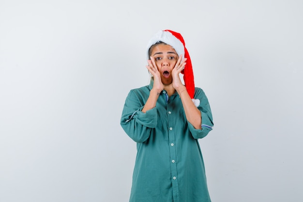 Giovane donna che grida tenendo le mani vicino alla bocca in camicia, cappello da babbo natale e sembra turbata, vista frontale.