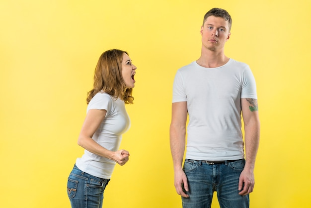 Young woman shouting on her boyfriend standing against yellow background
