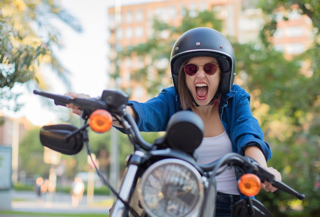 Young woman shouting on a motorbike