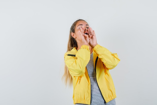 Молодая женщина кричит или объявляет что-то в футболке, куртке, вид спереди.
