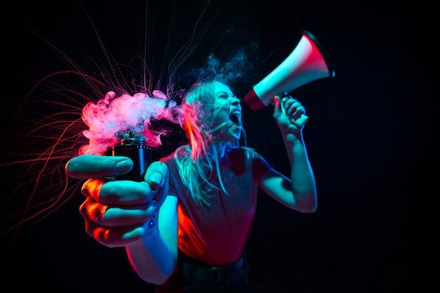 Молодая женщина кричит с мегафоном и дымом в неоновом свете на черном фоне
