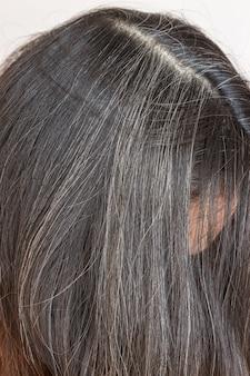 若い女性は彼女の灰色の髪を見せる。