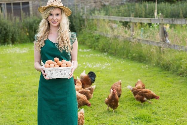 Молодая женщина показывает корзину, заполненную яйцами