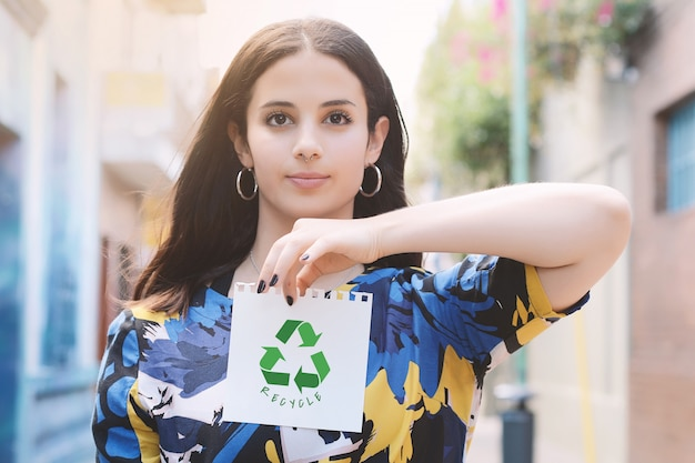 Молодая женщина показывая блокнот с рециркулировать символ