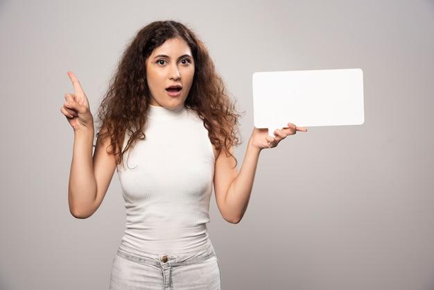 親指を上げて空白の白いポスターを保持している若い女性。高品質の写真