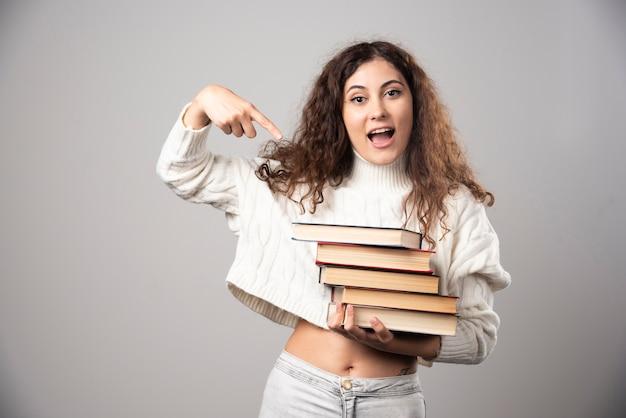 Молодая женщина показывает стопку книг на серой стене. фото высокого качества