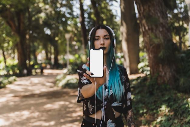 Молодая женщина показывает пустой белый смартфон с наушниками на голове