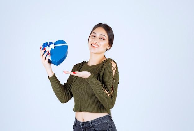 Giovane donna che mostra il contenitore di regalo blu su fondo bianco.
