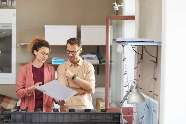 Young woman showing the blueprint in her hands and discussing it with her colleague while they working on printed machine