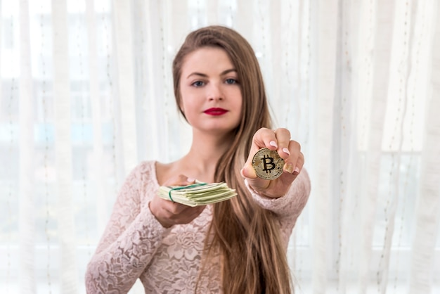 Young woman showing bundle of dollars and golden bitcoin