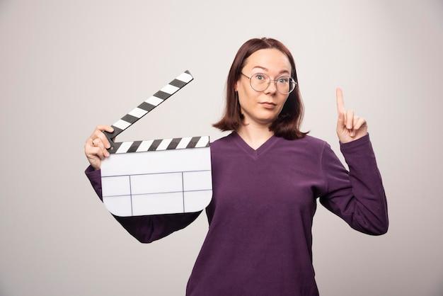 Giovane donna che mostra un nastro cinematografico su un bianco. foto di alta qualità