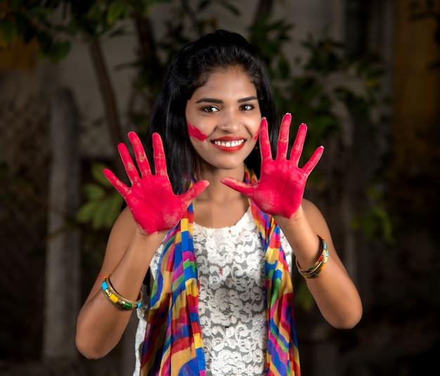 Молодая женщина показывает красочную ладонь и празднует холи с всплеском цвета
