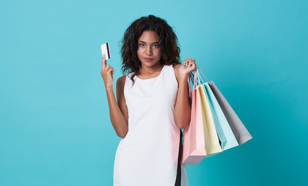 Young woman showing credit card and shopping bags isolated over blue