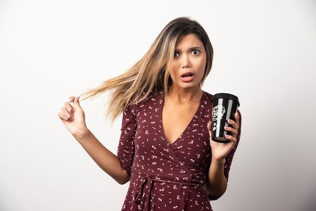 Giovane donna che mostra una tazza di bevanda sul muro bianco.