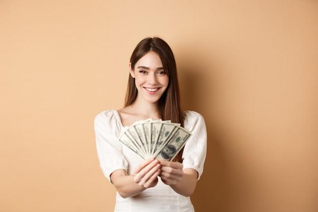 Молодая женщина показывает долларовые купюры и улыбается, стоя с деньгами на бежевом фоне. понятие ссуды и страхования.