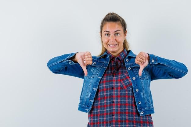 シャツ、ジャケット、幸せそうに見える、正面図で二重親指を示している若い女性。
