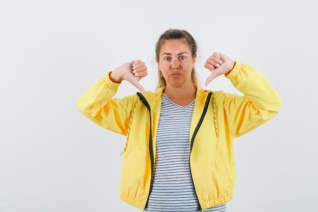 Tシャツ、ジャケット、自信を持って、正面図で二重親指を示している若い女性。