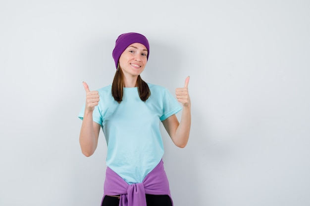 Young woman showing double thumbs up in blue t-shirt, purple beanie and looking cheery. front view.