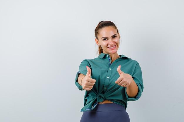 Молодая женщина показывает двойные пальцы вверх в зеленой рубашке и выглядит веселой. передний план.