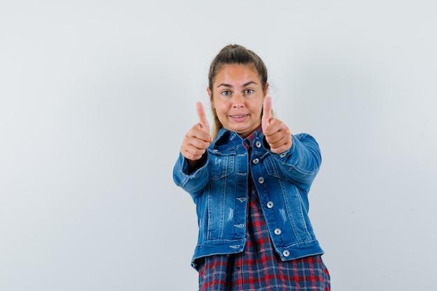 シャツ、ジャケット、自信を持って、正面図で二重親指を示す若い女性。
