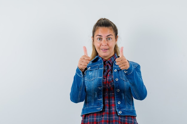 若い女性はシャツ、ジャケットで二重の親指を見せて、幸せそうに見えます。正面図。