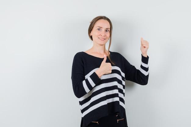 스트라이프 니트와 검은 색 바지에 두 엄지 손가락을 보여주는 젊은 여자와 행복을 찾고