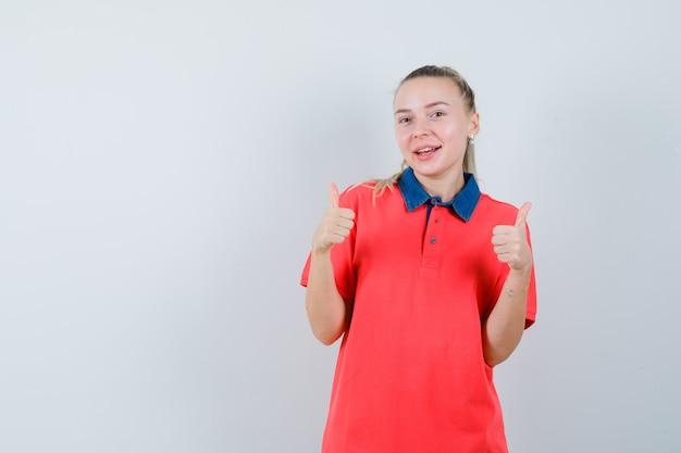 T- 셔츠에 두 엄지 손가락을 보여주는 쾌활한 찾고 젊은 여자