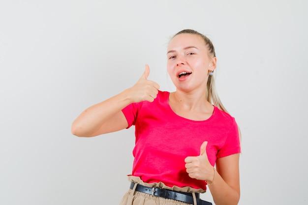 T- 셔츠와 바지에 두 엄지 손가락을 보여주는 젊은 여자와 메리 찾고