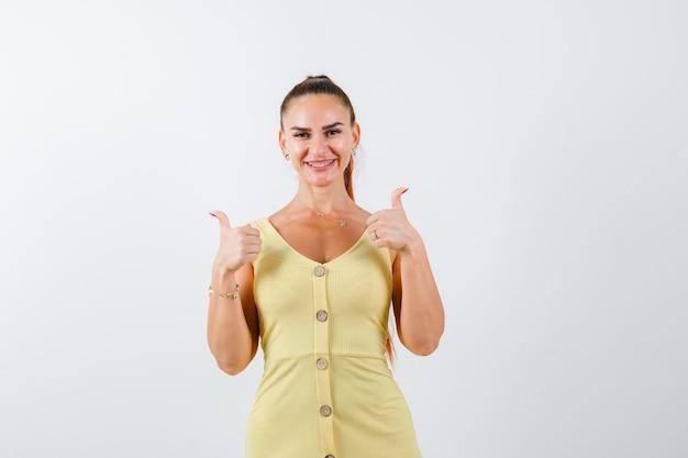Giovane donna che mostra i doppi pollici in su in vestito giallo e che sembra allegra. vista frontale.