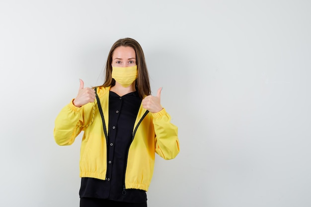 Young woman showing double thumbs up