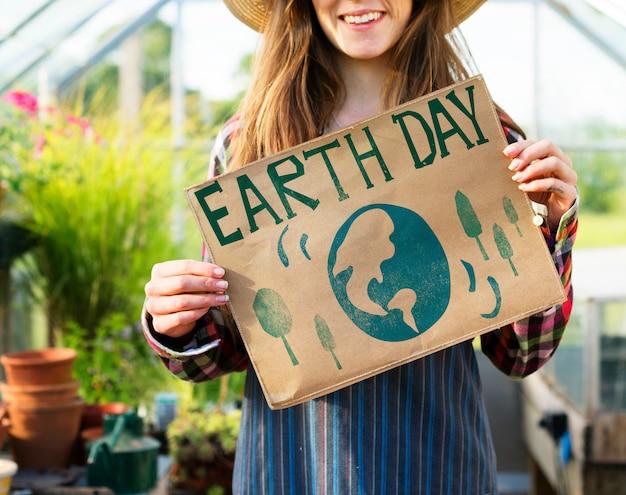 地球の日のポスターを示す若い女性