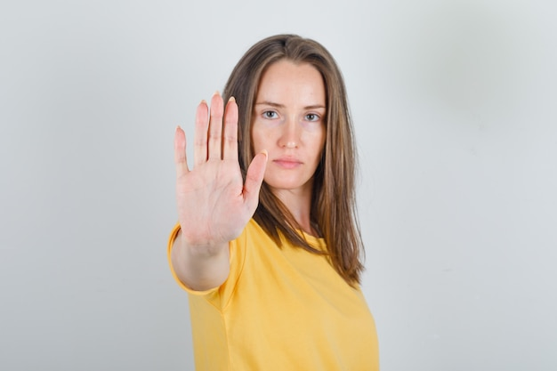 Young woman showing enough gesture with hand in yellow t-shirt and looking fatigued