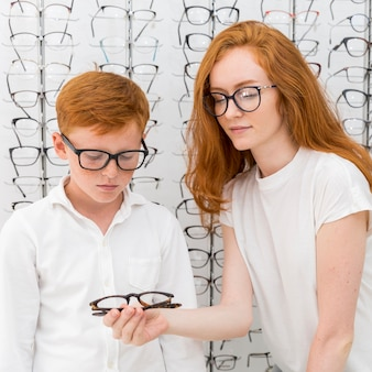 Young woman showing eyeglasses to freckle boy in optics store