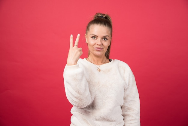 Молодая женщина показывает пальцы, делая знак победы