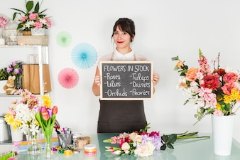 Young woman showing flowers in stock on slate