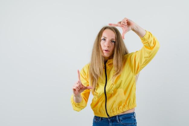 Молодая женщина показывает жест кадра в желтой куртке бомбардировщика и голубых джинсах и смотрит сосредоточенно, вид спереди.