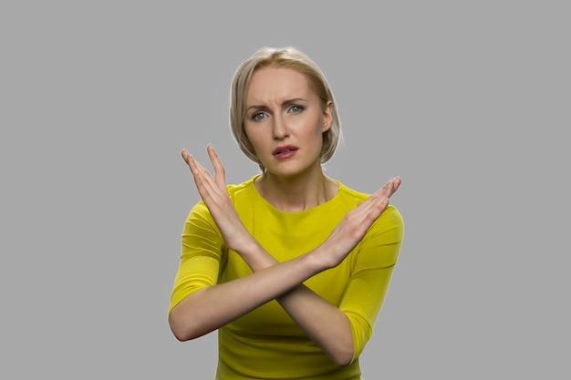 교차 손으로 제스처를 보여주는 젊은 여자. 회색 배경에 제스처를 금지하는 것을 보여주는 백인 여자.