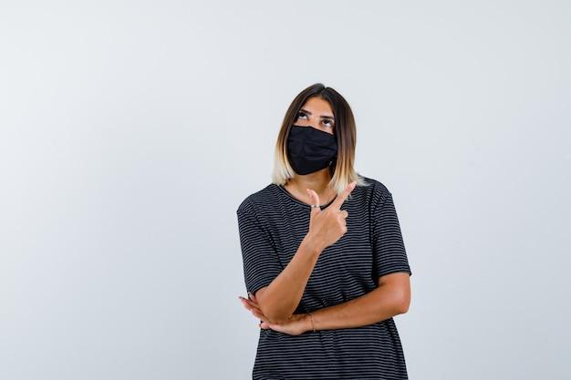 Giovane donna che mostra il gesto della pistola, tenendo la mano sotto il gomito in abito nero, maschera nera e guardando pensieroso, vista frontale.