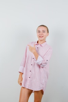 Молодая женщина показывает жест пистолета в розовой рубашке и выглядит веселой