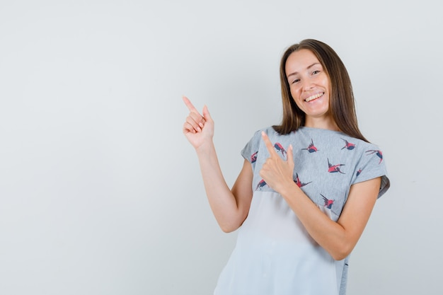 Young woman showing gun gesture in t-shirt and looking happy. front view.