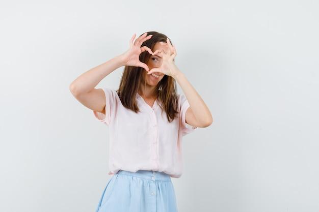 Tシャツ、スカート、陽気に見える、正面図でハートジェスチャーを示す若い女性。