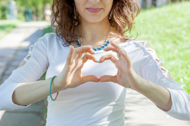 Молодая женщина показывает сердце в парке