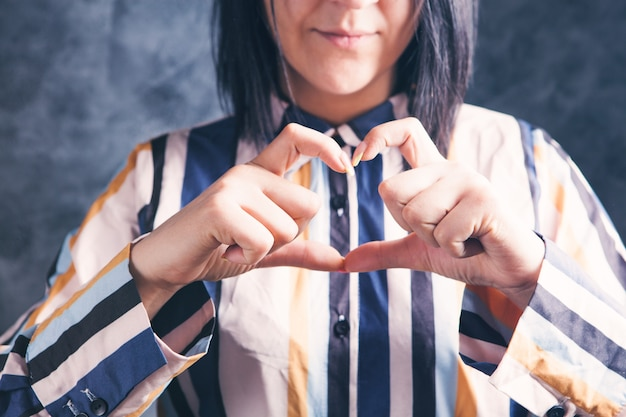 Young woman showing heart with her fingers