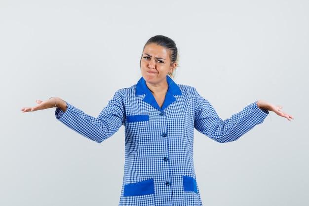 Giovane donna che mostra gesto impotente in camicia pigiama a quadretti blu e sembra incerta. vista frontale.