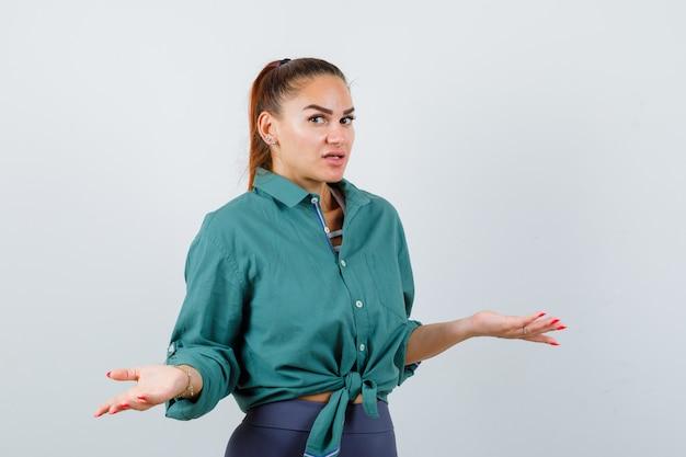 緑のシャツに肩をすくめて、混乱しているように見える、正面図で無力なジェスチャーを示す若い女性。