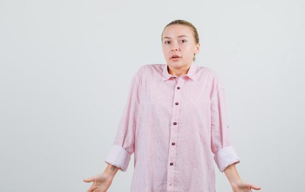 Молодая женщина в розовой рубашке показывает беспомощный жест и выглядит смущенной