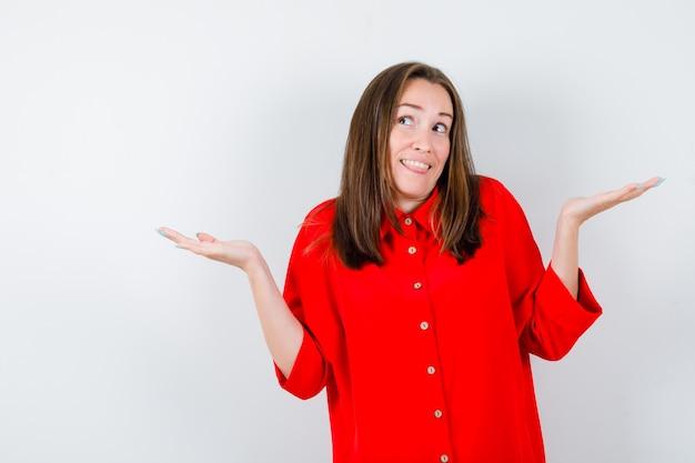 赤いブラウスで無力なジェスチャーを示し、優柔不断に見える若い女性。正面図。